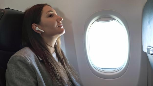 Jeune femme écoutant de la musique avec des écouteurs sans fil dans l'avion