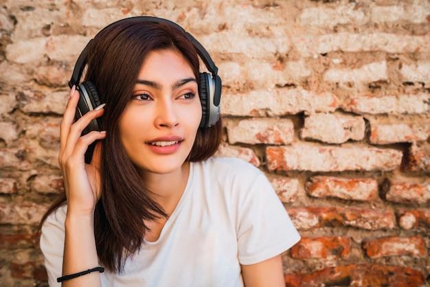 Jeune femme écoutant de la musique avec des écouteurs.