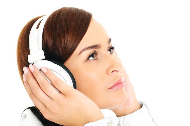 Une jeune femme écoutant de la musique sur fond whie