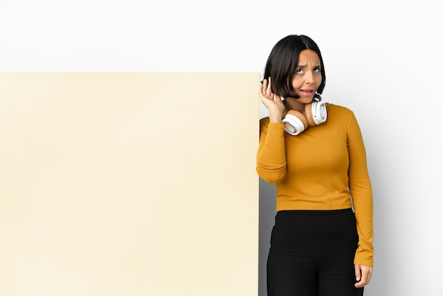 Jeune femme écoutant de la musique avec une grande pancarte vide sur fond isolé écoutant quelque chose en mettant la main sur l'oreille