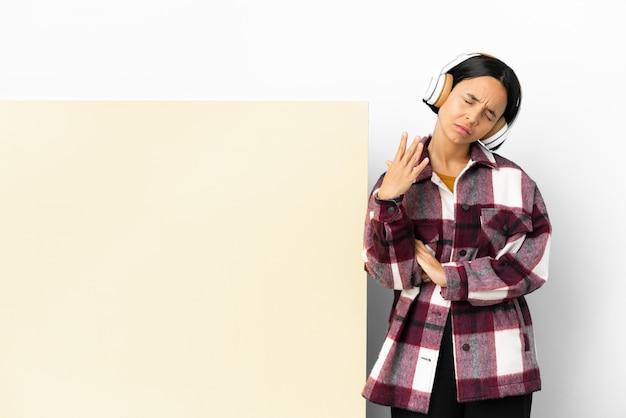 Jeune femme écoutant de la musique avec une grande pancarte vide sur fond isolé avec une expression fatiguée et malade