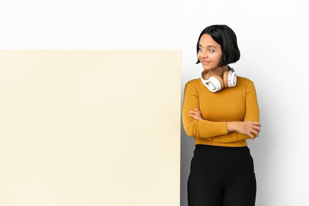 Jeune femme écoutant de la musique avec une grande pancarte vide sur fond isolé faisant des doutes à côté d'un geste