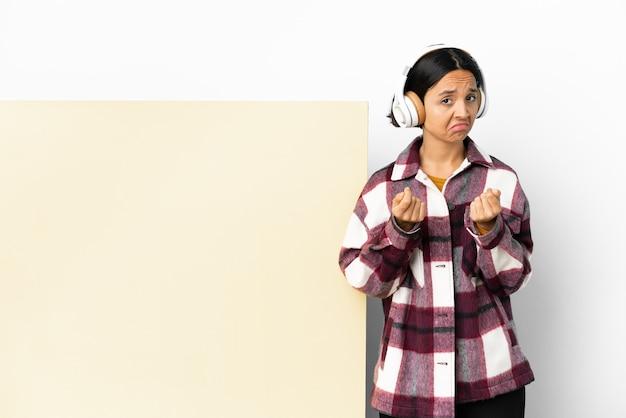 Jeune femme écoutant de la musique avec une grande pancarte vide sur fond isolé faisant un geste d'argent mais est ruinée
