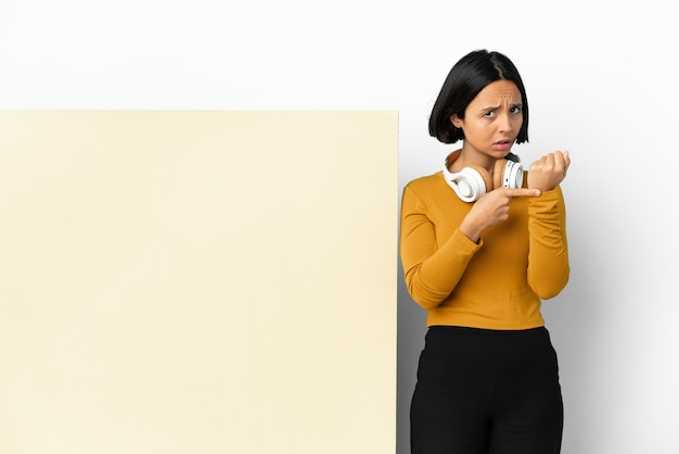 Jeune femme écoutant de la musique avec une grande pancarte vide sur fond isolé faisant le geste d'être en retard