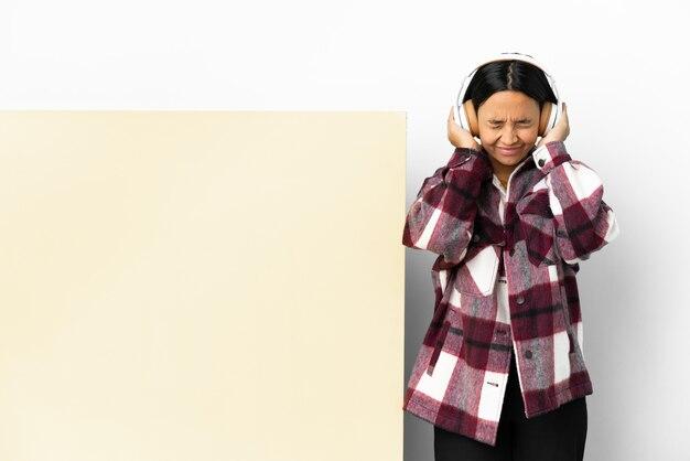 Jeune femme écoutant de la musique avec une grande pancarte vide sur fond isolé frustré et couvrant les oreilles