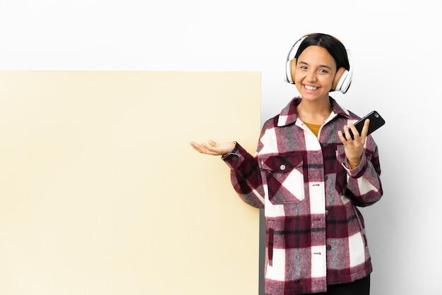 Jeune femme écoutant de la musique avec une grande pancarte vide sur fond isolé en gardant une conversation avec le téléphone portable avec quelqu'un