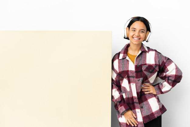 Jeune femme écoutant de la musique avec une grande pancarte vide sur fond isolé posant avec les bras à la hanche et souriant