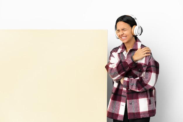 Jeune femme écoutant de la musique avec une grande pancarte vide sur fond isolé souffrant de douleurs à l'épaule pour avoir fait un effort