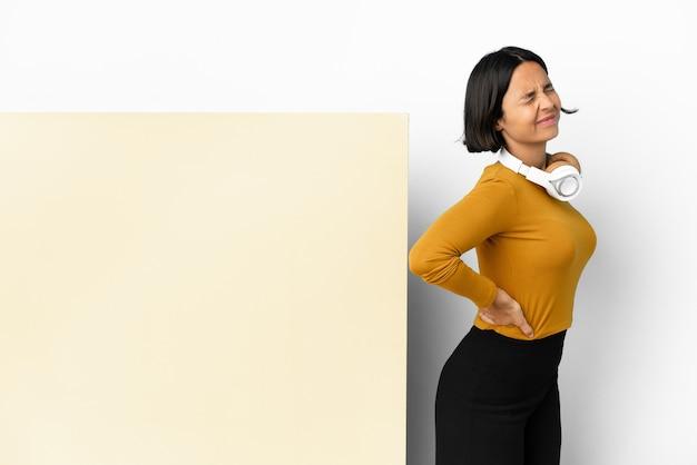 Jeune femme écoutant de la musique avec une grande pancarte vide fond isolé souffrant de maux de dos pour avoir fait un effort