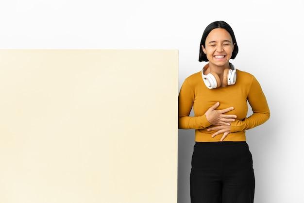 Jeune femme écoutant de la musique avec une grande pancarte vide sur fond isolé souriant beaucoup