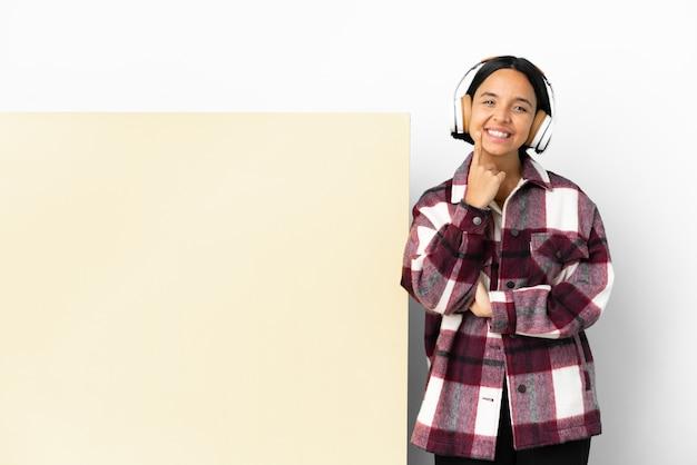 Jeune femme écoutant de la musique avec une grande pancarte vide sur fond isolé souriant avec une expression heureuse et agréable