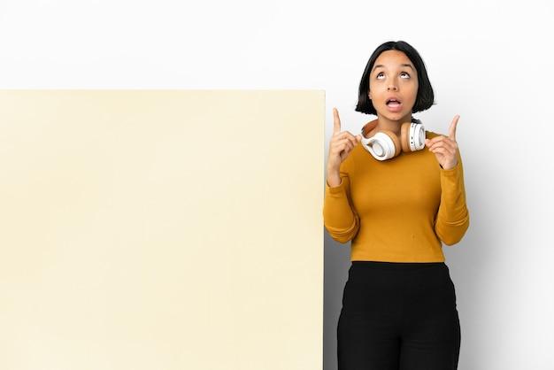 Jeune femme écoutant de la musique avec une grande pancarte vide sur fond isolé surpris et pointant vers le haut