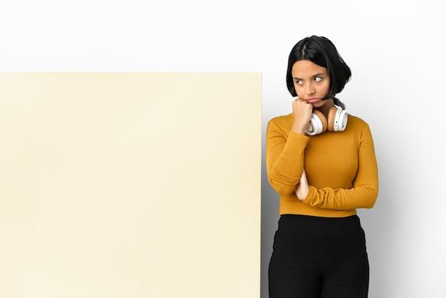 Jeune femme écoutant de la musique avec une grande pancarte vide sur un mur isolé avec une expression fatiguée et ennuyée