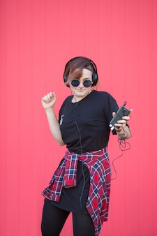 Jeune femme écoutant de la musique avec de gros écouteurs sur un mur rose