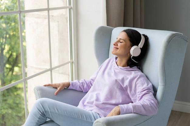 Jeune femme écoutant de la musique à la maison