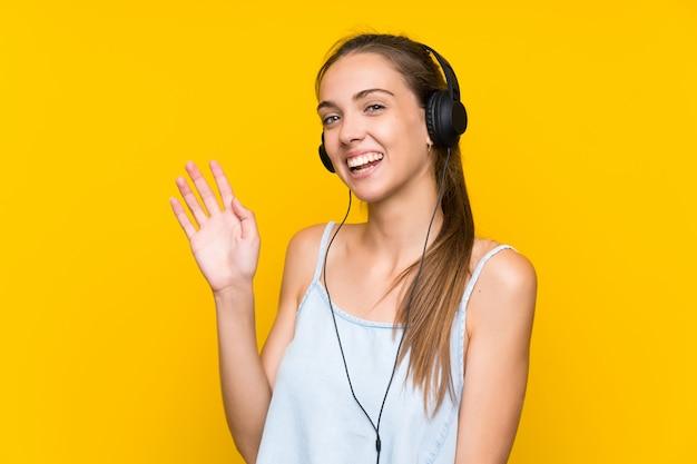 Jeune femme écoutant de la musique sur un mur jaune isolé, saluant avec la main avec une expression heureuse