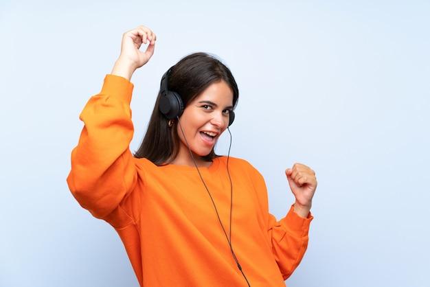 Jeune femme écoutant de la musique avec un téléphone portable sur un mur bleu isolé célébrant une victoire