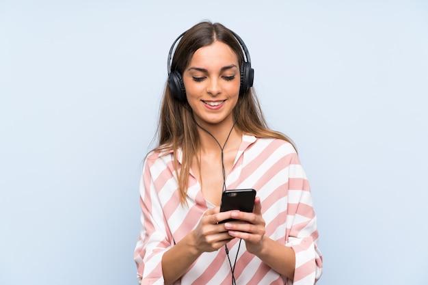 Jeune femme écoutant de la musique avec un téléphone portable