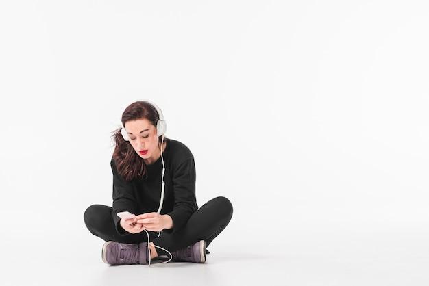 Jeune femme écoutant de la musique à travers un casque sur un lecteur mp3