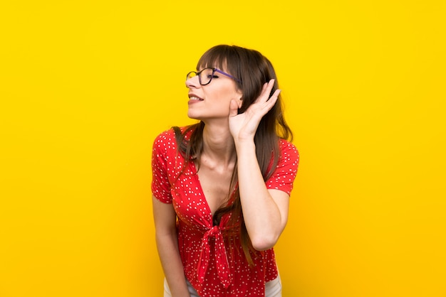 Jeune femme écoutant quelque chose en mettant la main sur l'oreille
