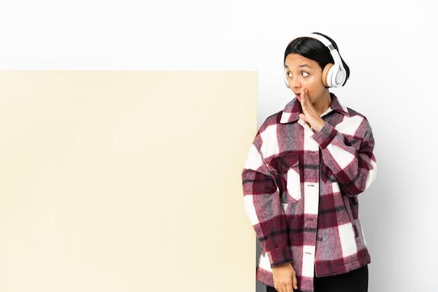 Jeune femme à l'écoute de la musique avec une grande pancarte vide sur fond isolé chuchotant quelque chose avec un geste de surprise tout en regardant sur le côté