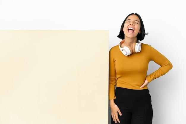 Jeune femme à l'écoute de la musique avec une grande pancarte vide sur fond isolé criant à l'avant avec la bouche grande ouverte