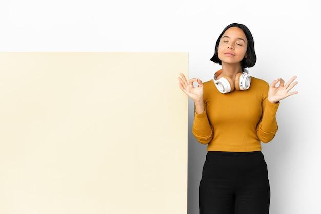 Jeune femme à l'écoute de la musique avec une grande pancarte vide sur fond isolé dans la pose zen