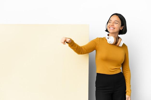 Jeune femme à l'écoute de la musique avec une grande pancarte vide sur fond isolé donnant un geste de pouce en l'air