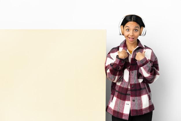 Jeune femme à l'écoute de la musique avec une grande pancarte vide sur fond isolé avec une expression faciale surprise