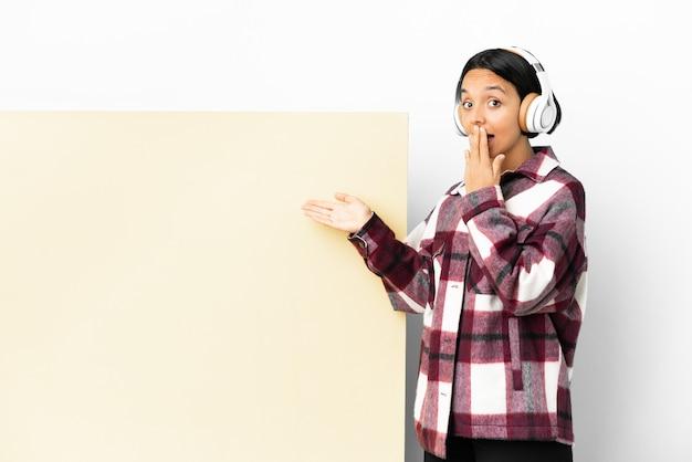 Jeune femme à l'écoute de la musique avec une grande pancarte vide sur fond isolé avec une expression de surprise tout en pointant le côté