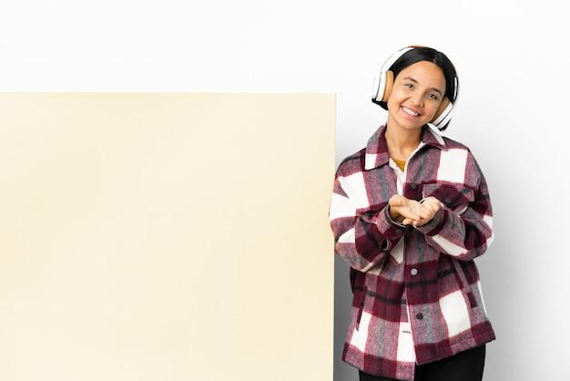 Jeune femme à l'écoute de la musique avec une grande pancarte vide sur fond isolé holding copyspace imaginaire sur la paume pour insérer une annonce