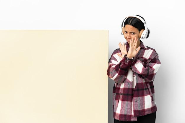 Jeune femme à l'écoute de la musique avec une grande pancarte vide sur fond isolé nerveux s'étendant les mains vers l'avant