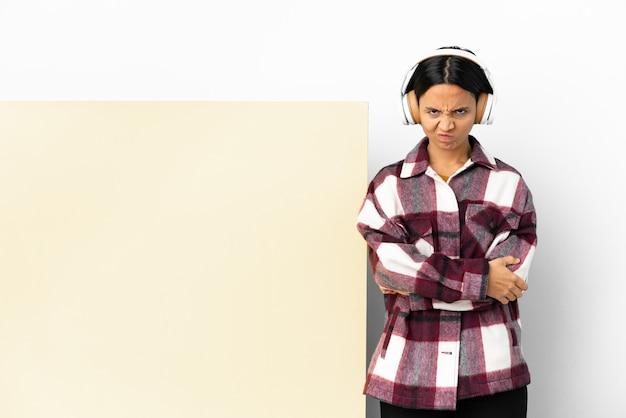 Jeune femme à l'écoute de la musique avec une grande pancarte vide sur un mur isolé se sentir bouleversé
