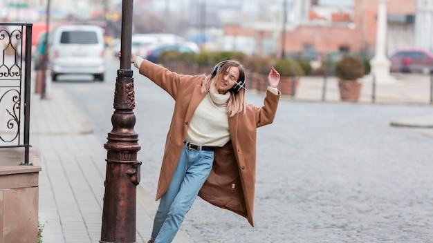 Jeune femme, écouter musique, sur, écouteurs, dans ville