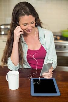 Jeune femme, écouter musique, sur, smartphone, à, tablette, et, tasse café, sur, worktop cuisine