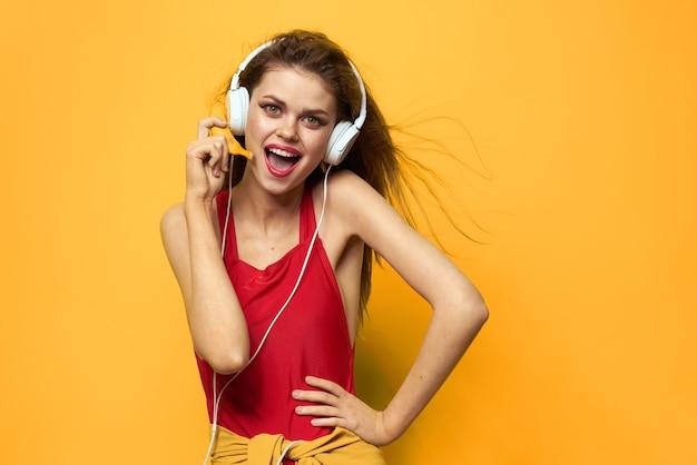 Jeune, femme, écouteurs, amusement, rire, maillot de bain, jaune