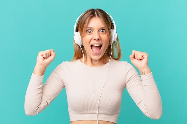 Jeune femme avec des écouteurs criant agressivement avec une expression fâchée
