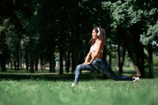Jeune femme avec des écouteurs effectuant des squats à l'extérieur