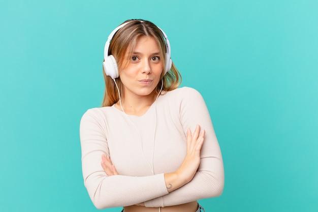 Jeune femme avec des écouteurs haussant les épaules, se sentant confuse et incertaine