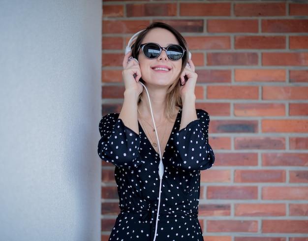 Jeune femme, à, écouteurs, et, lunettes soleil, sur, mur brique