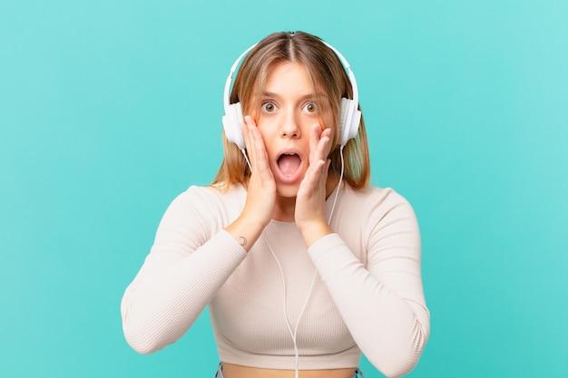 Jeune femme avec des écouteurs se sentant choquée et effrayée