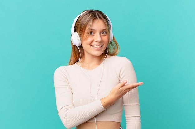 Jeune femme avec des écouteurs souriant gaiement, se sentant heureuse et montrant un concept