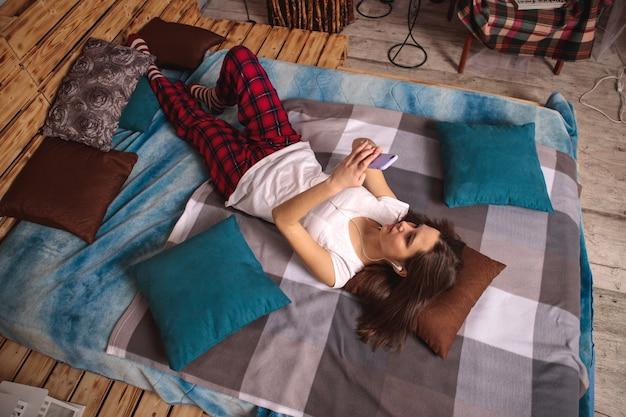 Une jeune femme avec des écouteurs et un téléphone portable dans les mains est allongée sur le lit et prend un selfie. la fille se prend en photo au téléphone et sourit.
