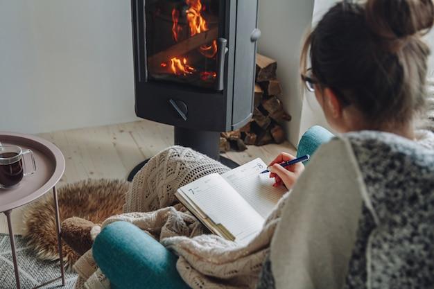 Jeune femme écrire dans un cahier assis dans un fauteuil par cheminée