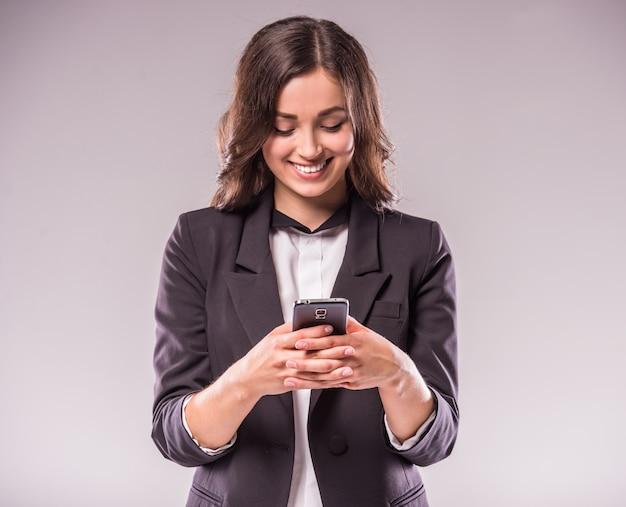 Jeune femme écrit un message avec smartphone.