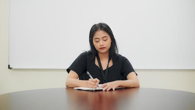 Jeune femme écrit ses devoirs sur la table