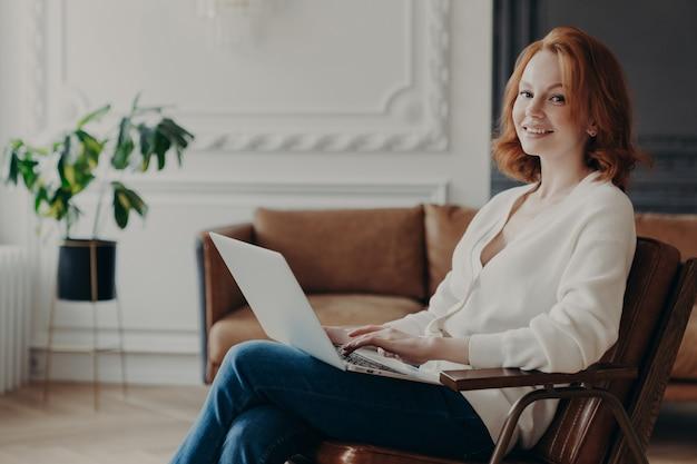 Jeune femme écrivain qualifiée tape ou claviers texte pour un nouveau livre sur un ordinateur portable, se sent à l'aise dans une chambre confortable, recherche des informations sur internet, travaille à la maison. étudiant occupé avec des cours