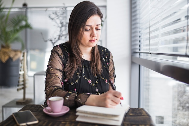 Jeune femme écrivant dans le journal au restaurant