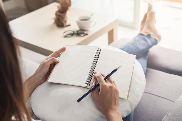 Jeune femme écrivant journal à la maison confortable sur le canapé dans le salon