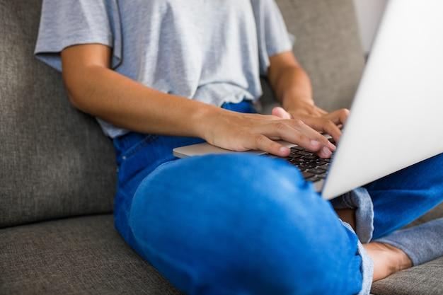 Jeune femme écrivant sur ordinateur à la maison